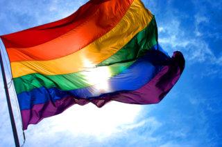 Rainbow flag with blue skies